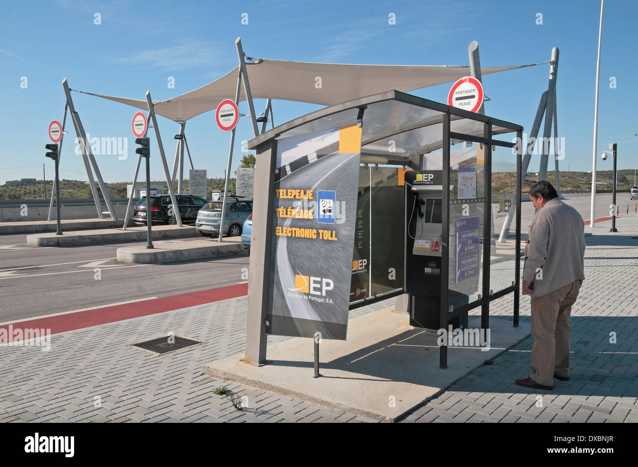 Man reading the instructions at an Electronic Toll point on the A22 motorway in southern Portugal (Algave). - Stock Image