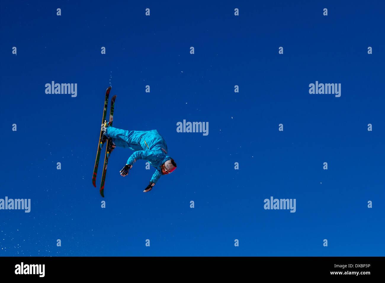 Ski instructor practising and demonstrating ski jumping, landing on a giant airbag - Stock Image