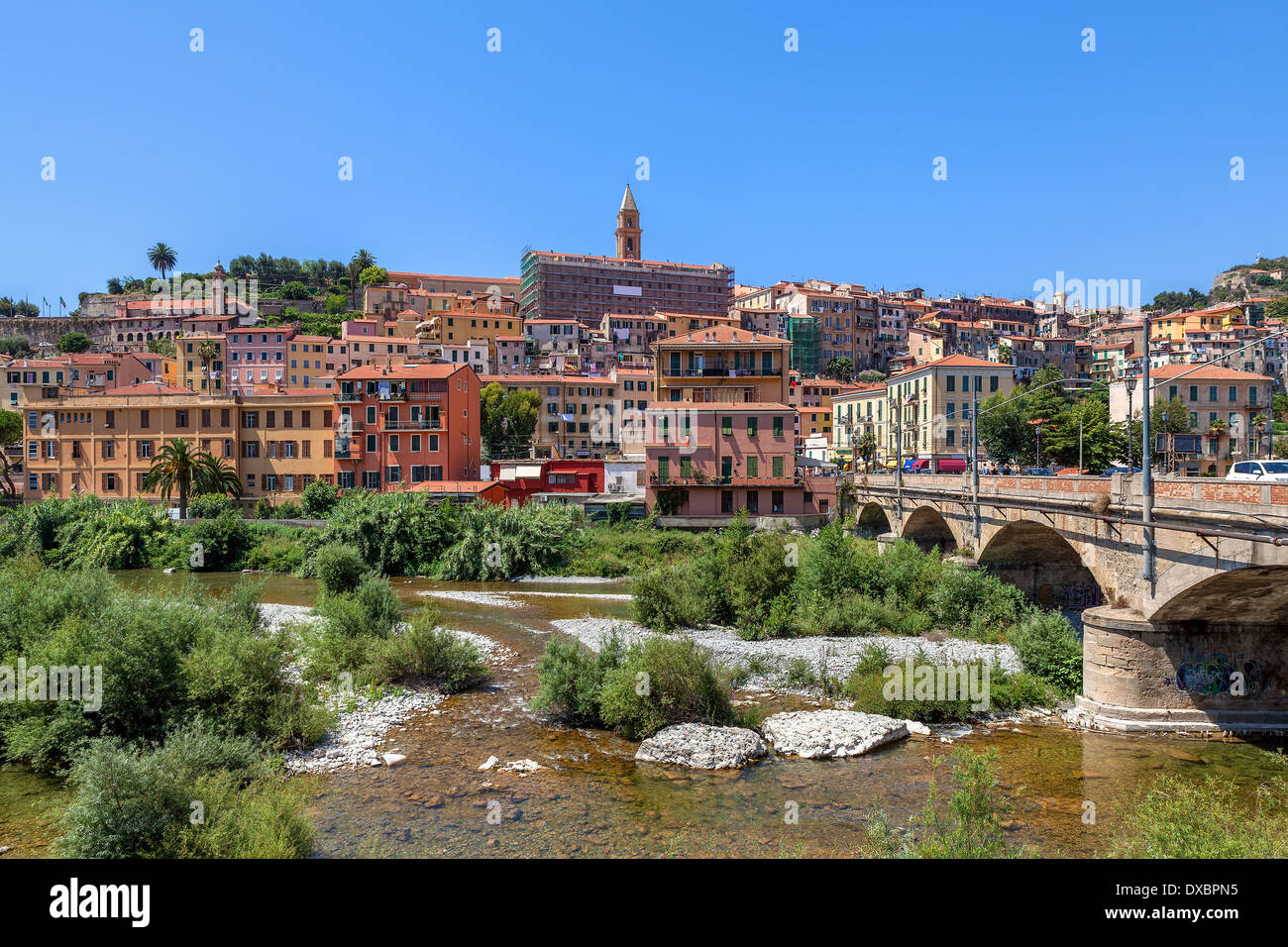 Urban bridge across riverbed overgrown with trees, shrubs and grass and old town of Ventimiglia under blue sky in Italy. - Stock Image