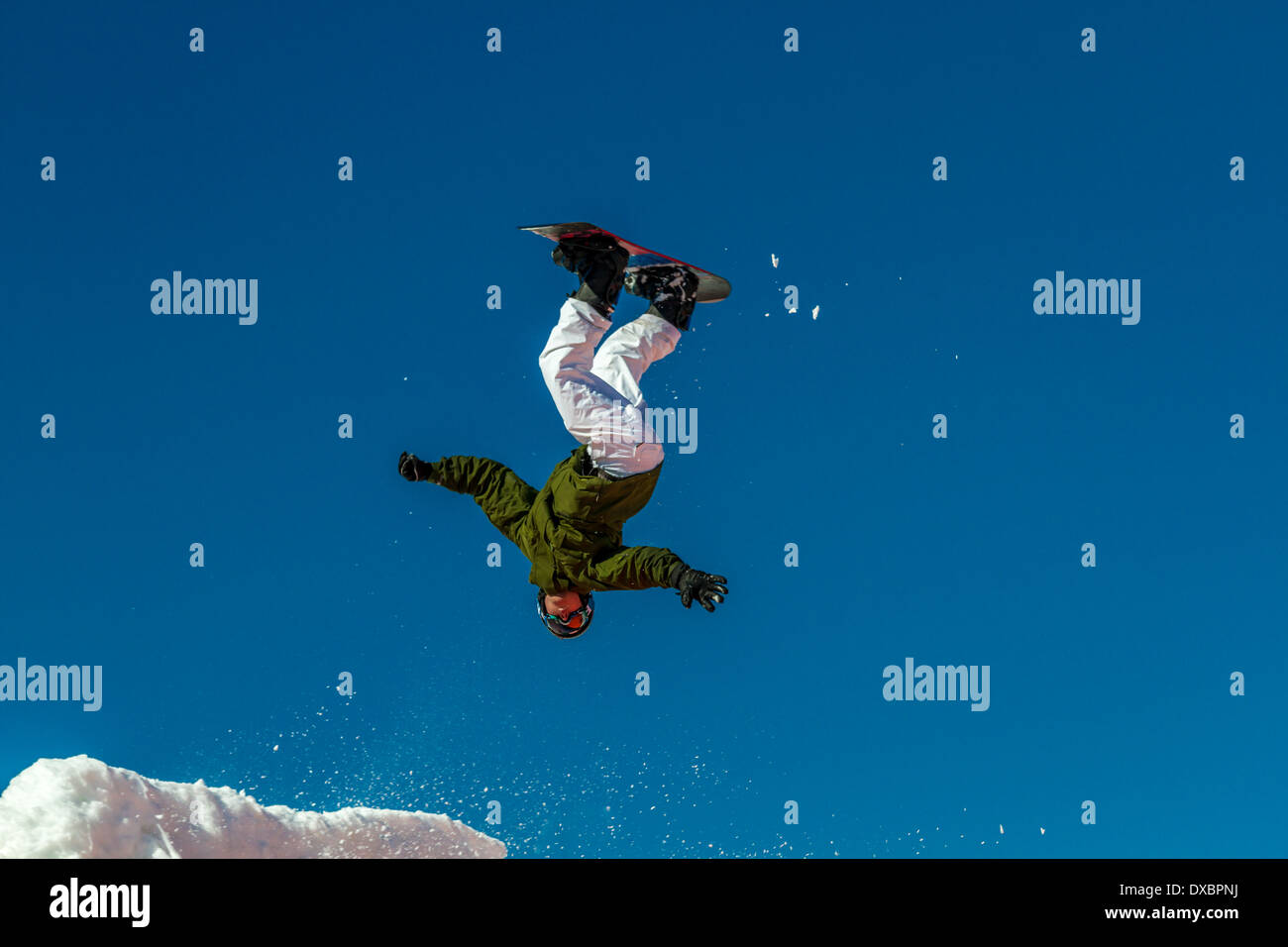 Person learning to snowboard jump: Airborne snowboarder upside down after taking off on a jump - Stock Image