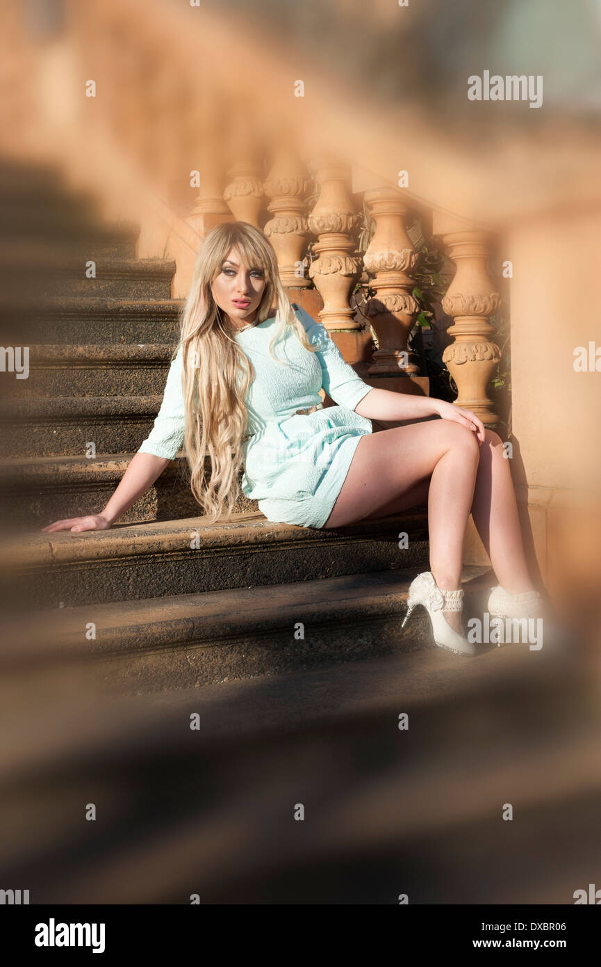 young woman sitting outside on sweeping stone staircase with blurred out surroundings - Stock Image