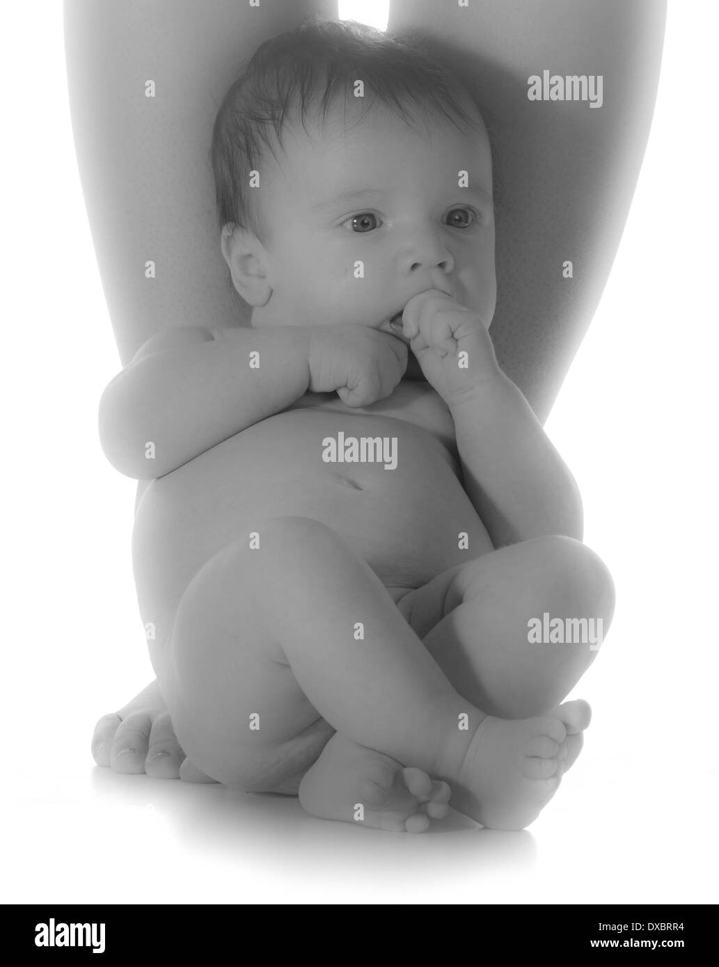 newborn baby sitting by mom's feet isolated in black and white - Stock Image
