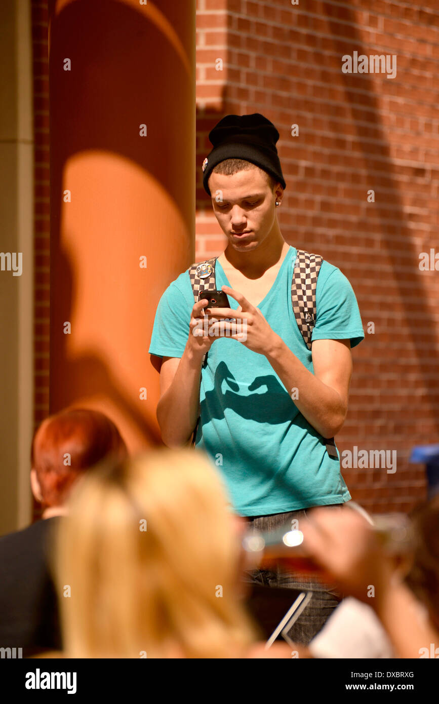 A young man on a texting on a college campus. Stock Photo