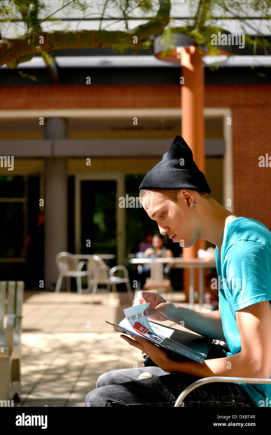 A young man on a college campus looking through educational brochures. Stock Photo