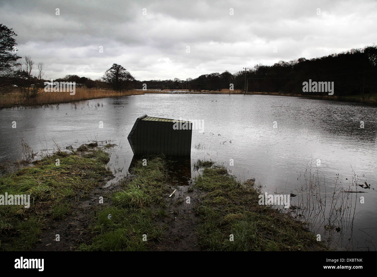 River Meon flooding in Titchfield, Hampshire, England - February 2014; toppled garden shed in flooded field. Stock Photo