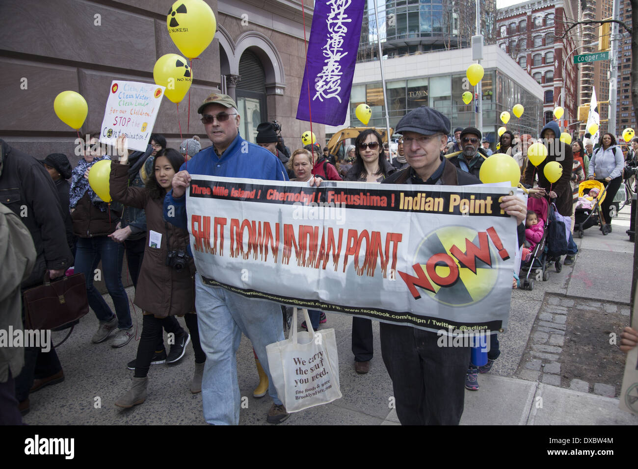 Antinuclear demonstrators march in NYC on the third anniversary of the ongoing nuclear meltdown disaster at Fukushima, Japan. - Stock Image