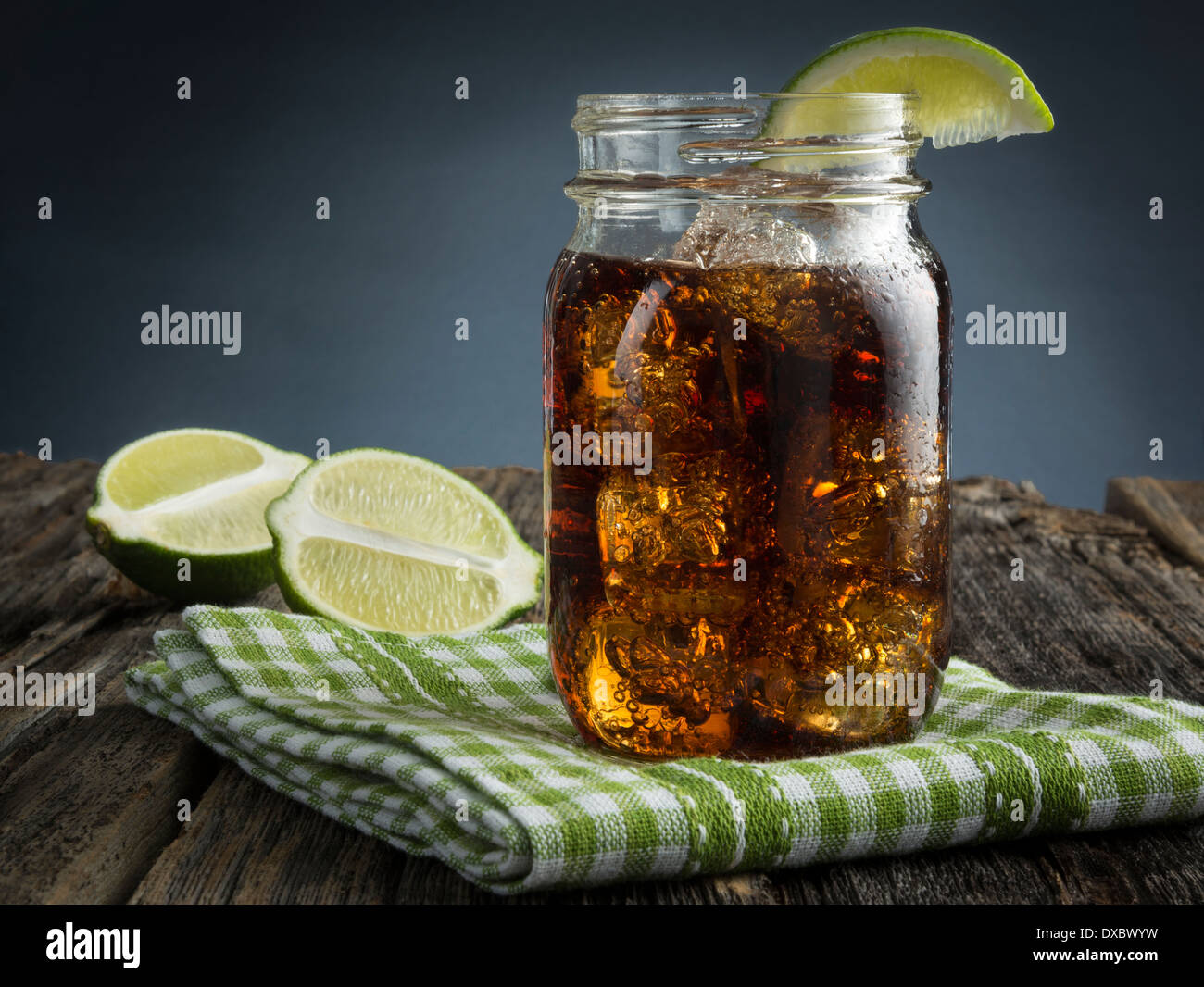 Cuba Libre or rum and cola drink with ice and lime in mason jar - Stock Image
