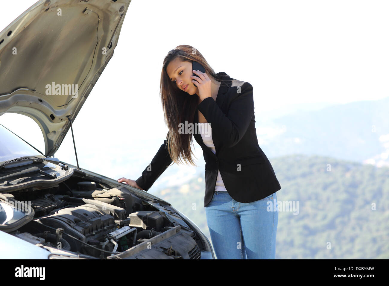 Woman on the phone looking her crash breakdown car in a road in the middle of the mountain - Stock Image
