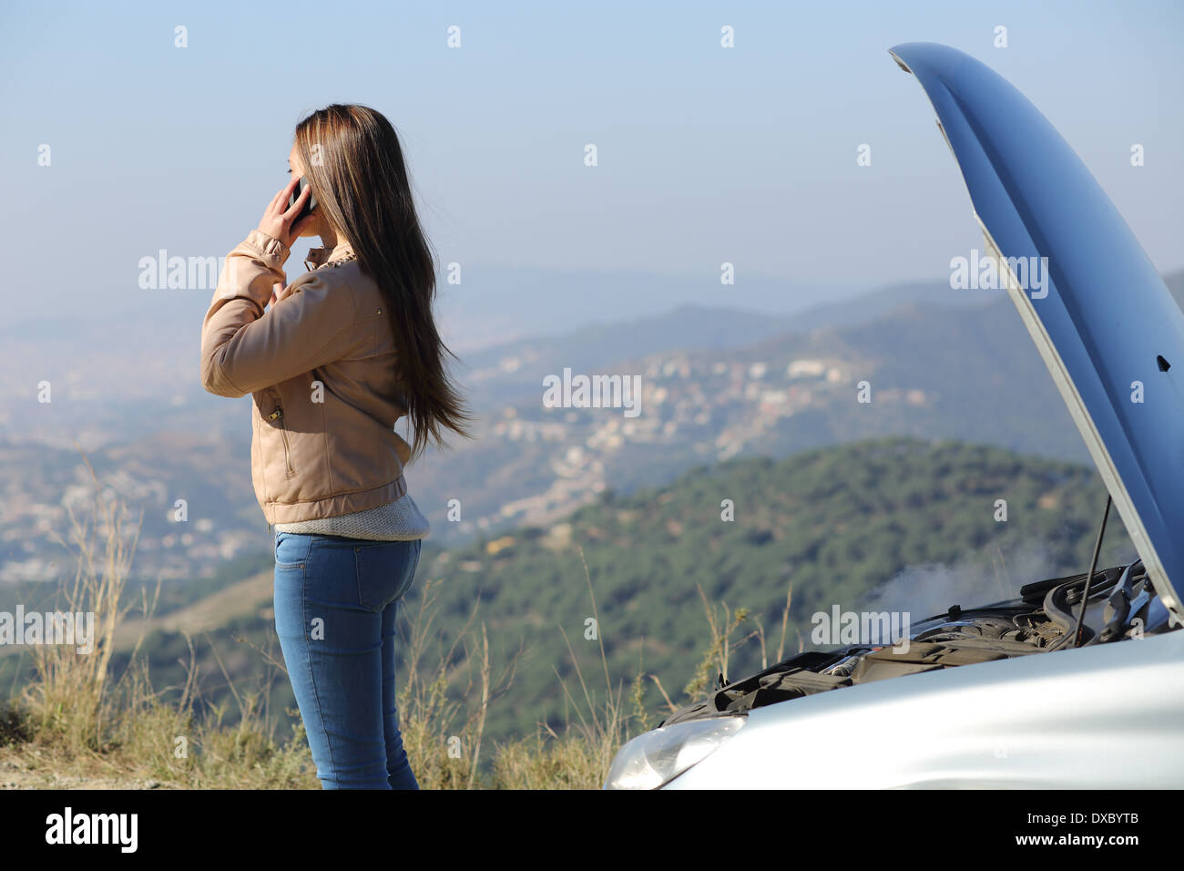 Woman on the phone asking for assistance beside her crashed breakdown car in a mountain road - Stock Image