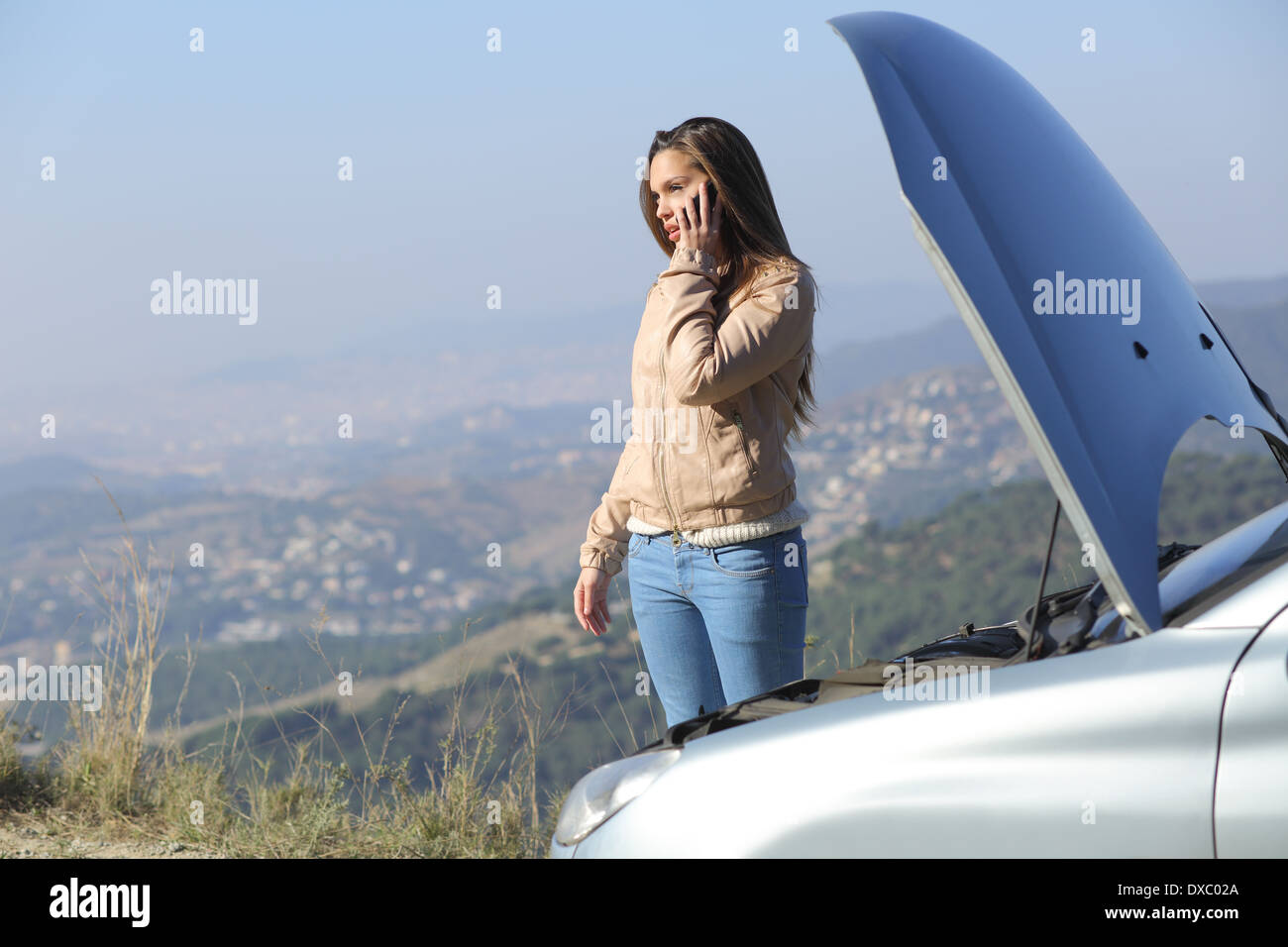 Woman on the phone asking for help beside her crash breakdown car in a road with a city in the background - Stock Image