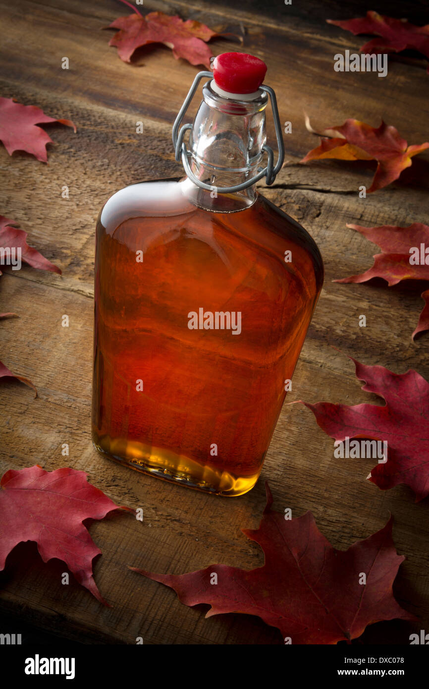 Organic maple syrup on wooden background with maple leaves - Stock Image