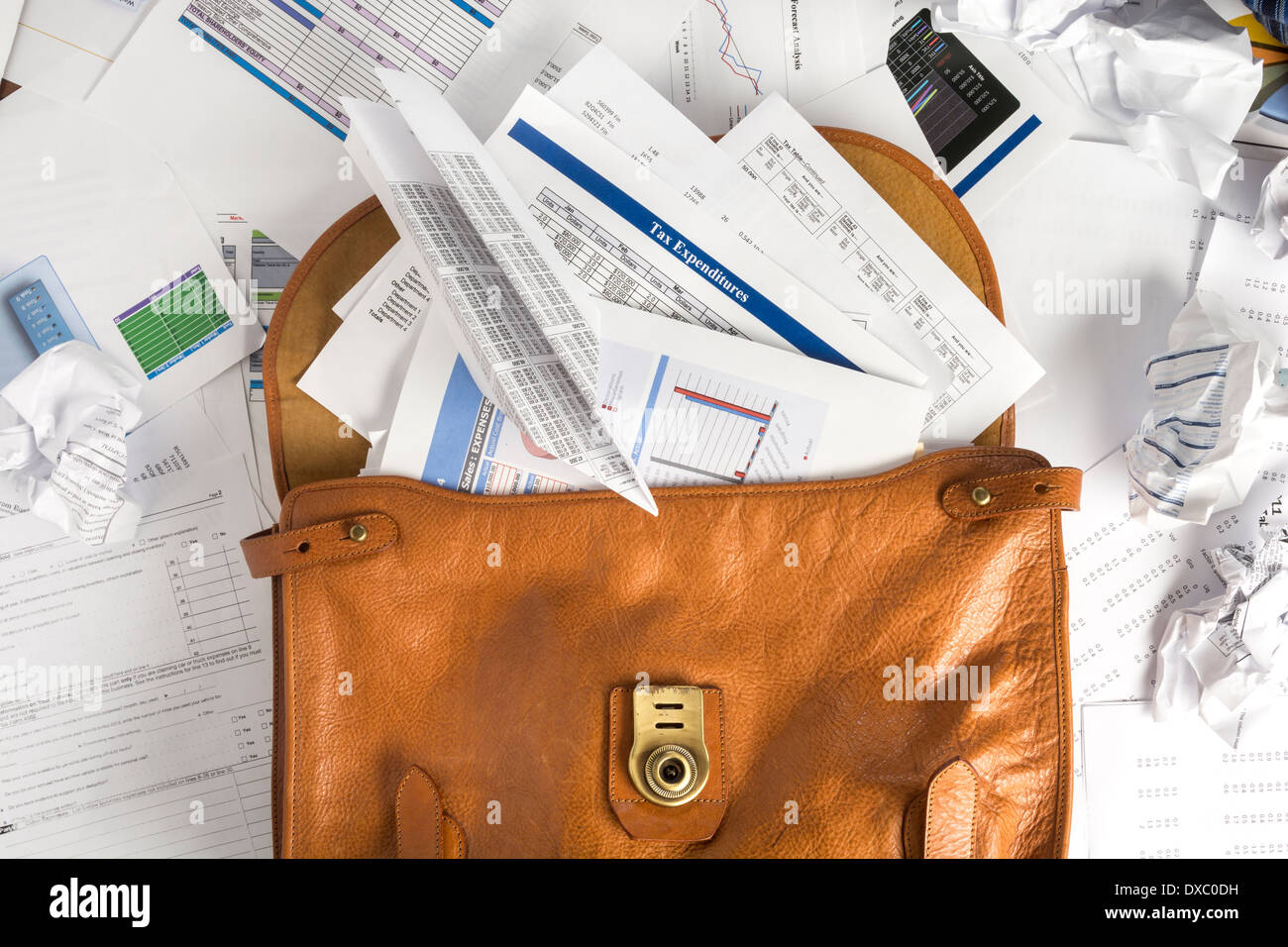 Concept photo showing briefcase open and overflowing with paperwork which can be used with tax or other financial stories - Stock Image