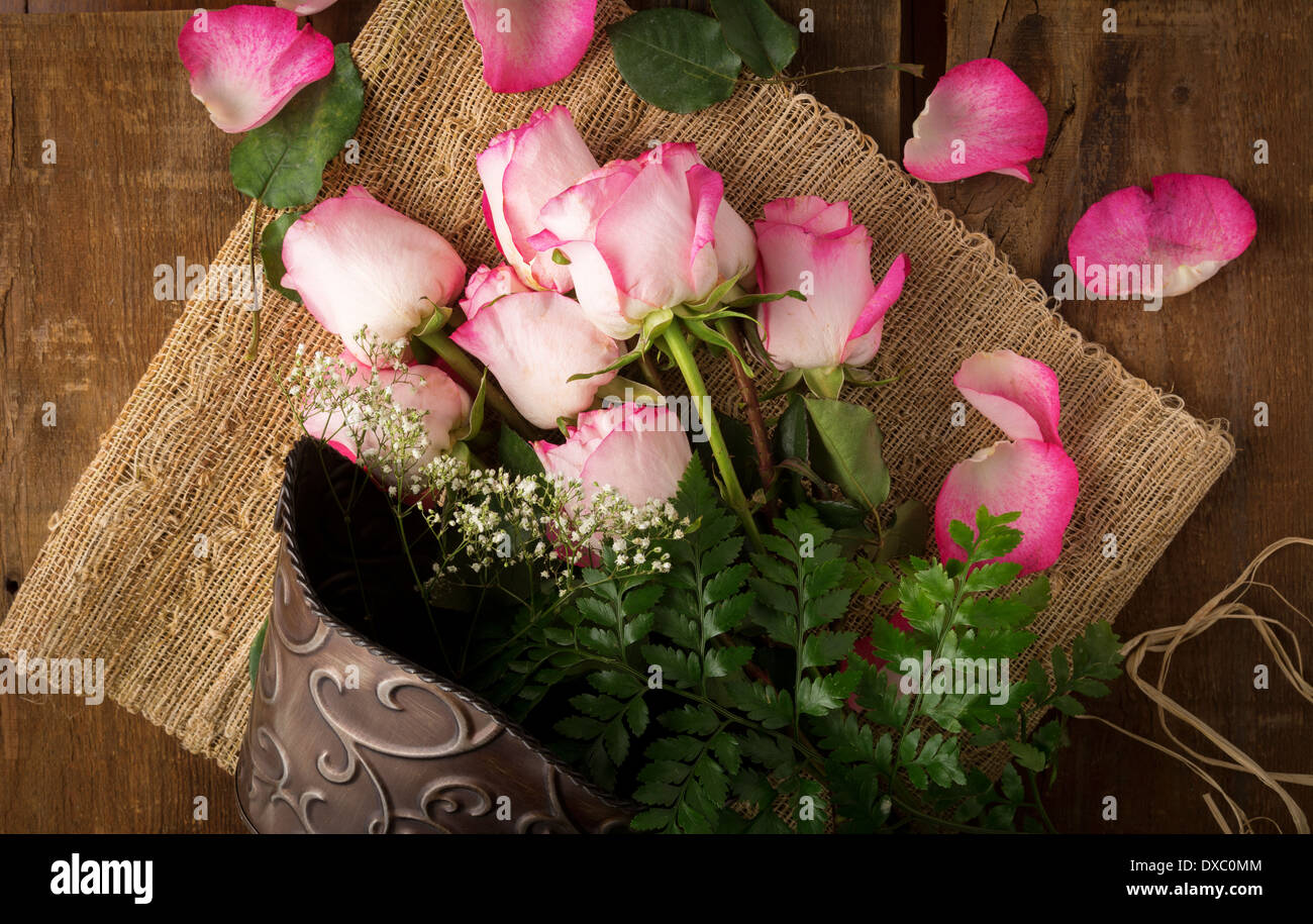 Pink roses on burlap and metal bucket ready to arrange shot from above Stock Photo