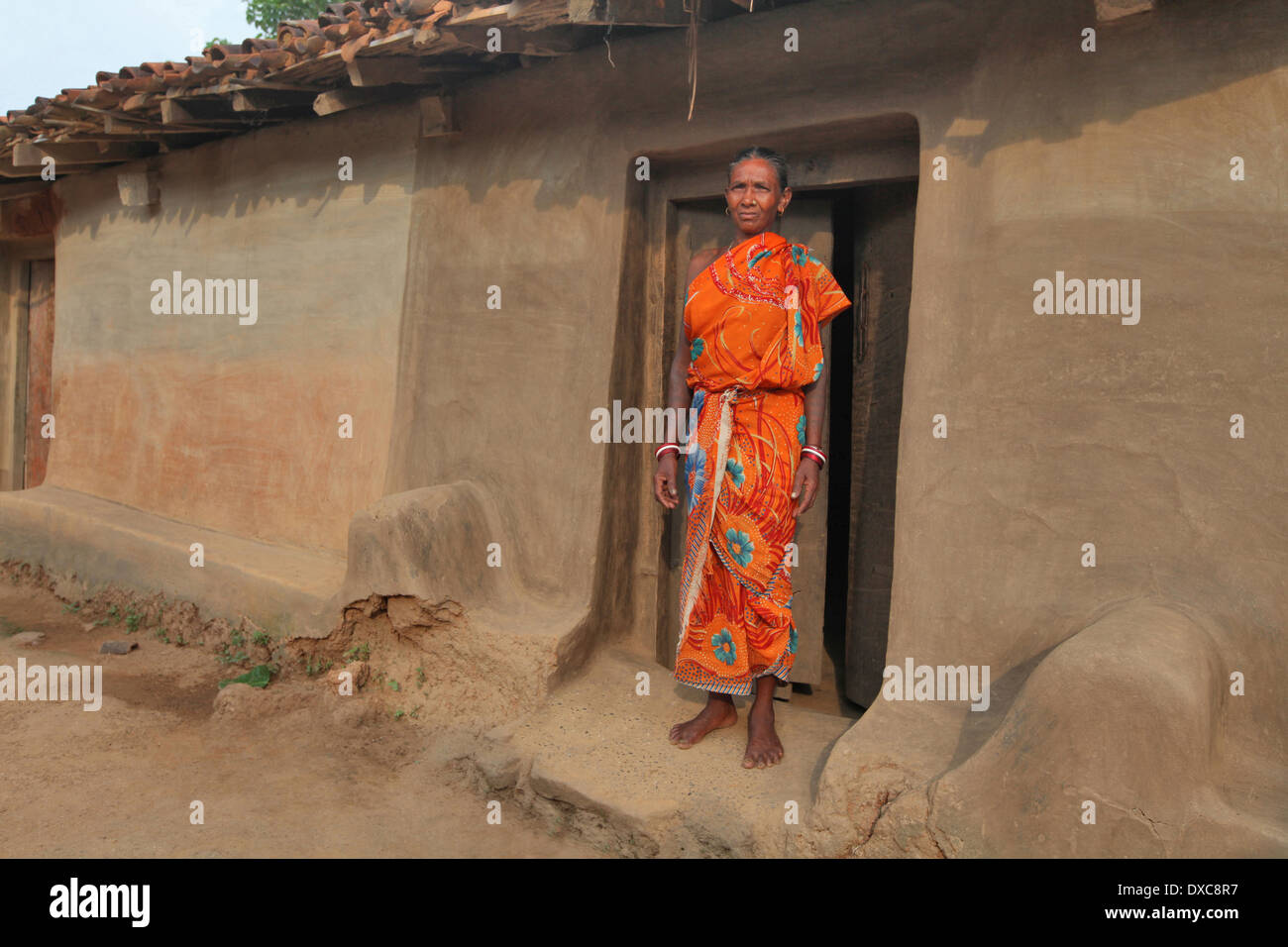 Woman in red sari standing in front of her mud house entrance. santhal tribe, Hardhekitand village, Jharkhand, India - Stock Image