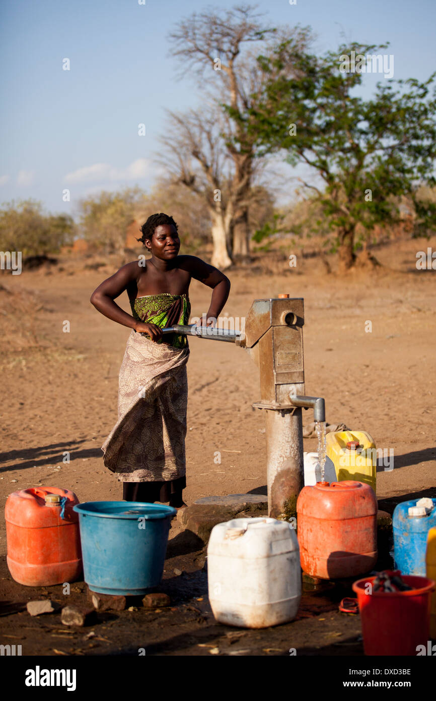 Africa woman pumping water at a stand pipe - Stock Image