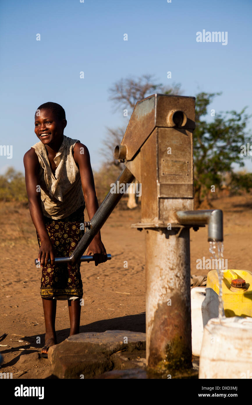 Africa child collecting water at a stand pipe - Stock Image