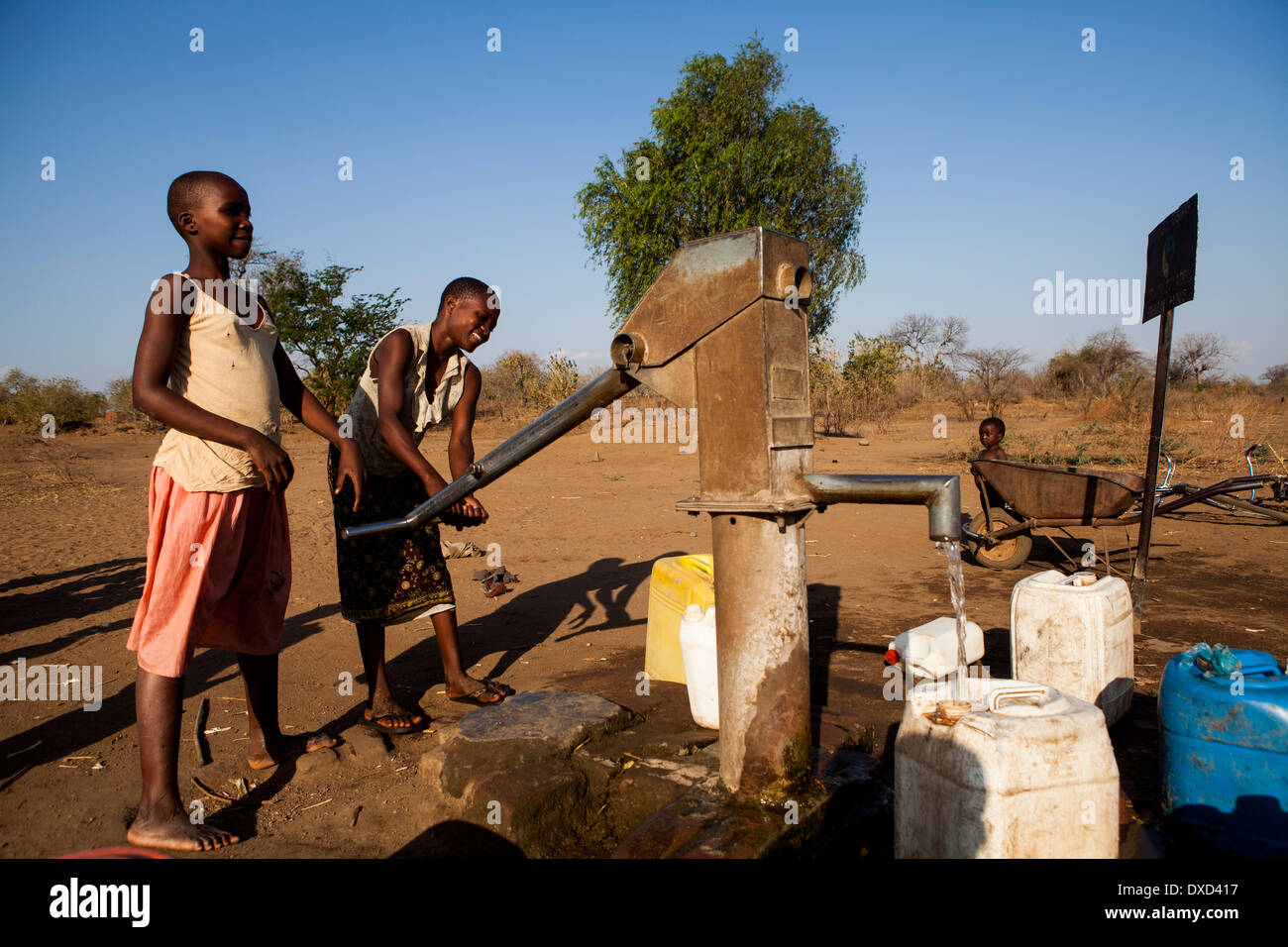 Africa children collecting water at a stand pipe - Stock Image