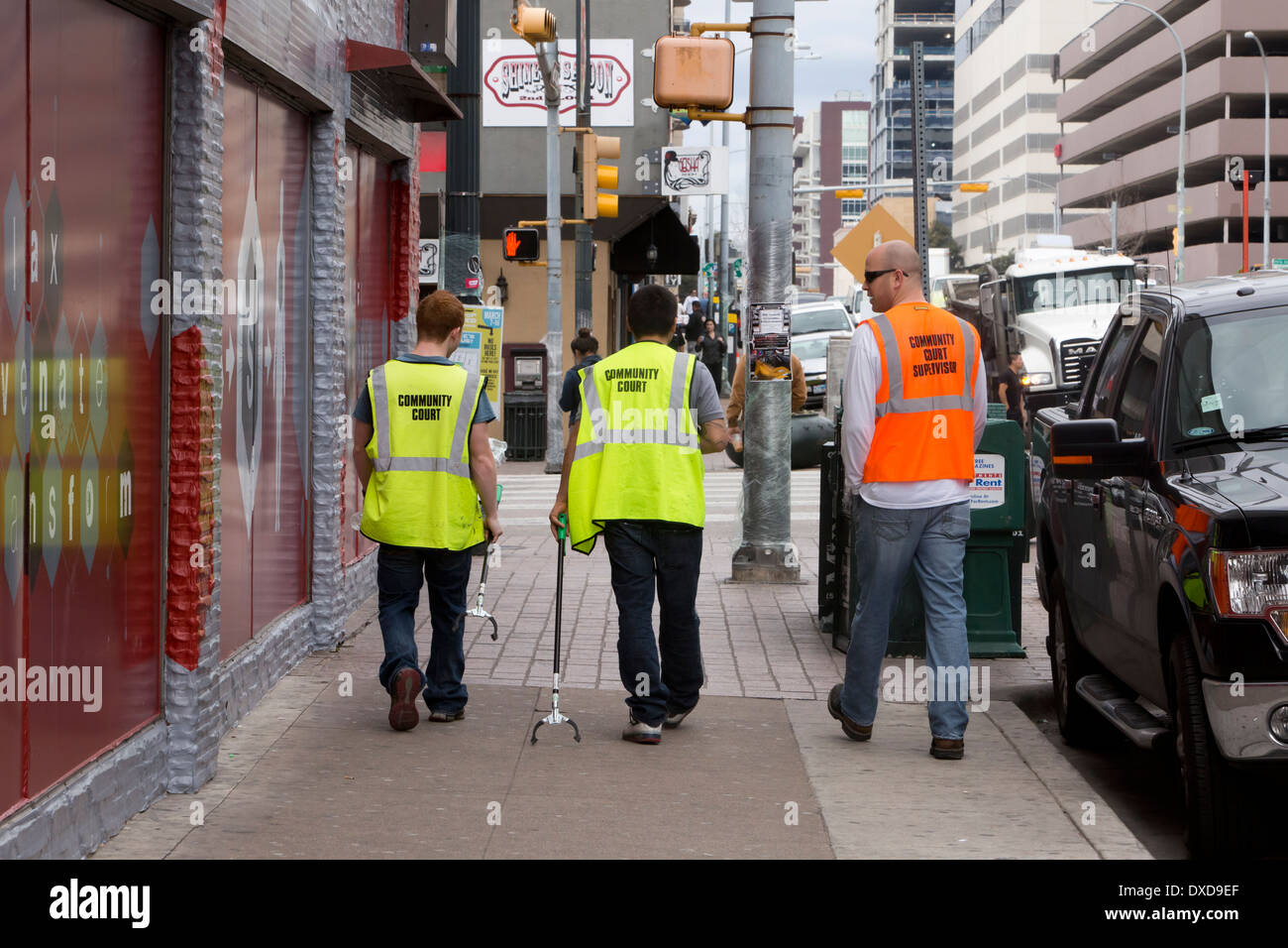 Young adult males use reach and pick-up tool to pick-up trash as part of their community service in downtown Austin, Texas - Stock Image