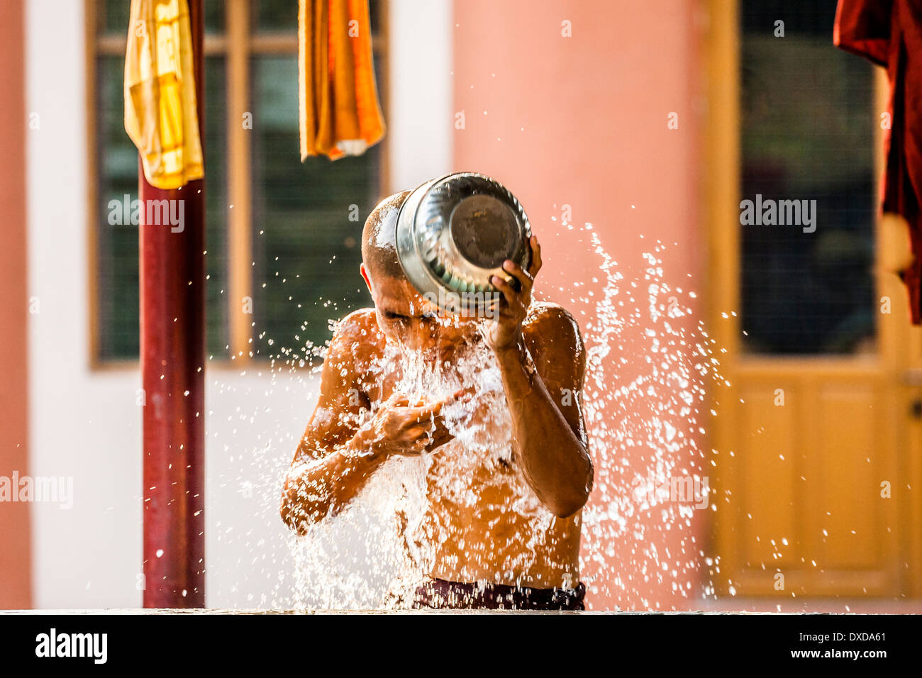 A monk uses a metal bowl to shower during a hot afternoon in Mandalay, Myanmar (Burma) in Southeast Asia. - Stock Image