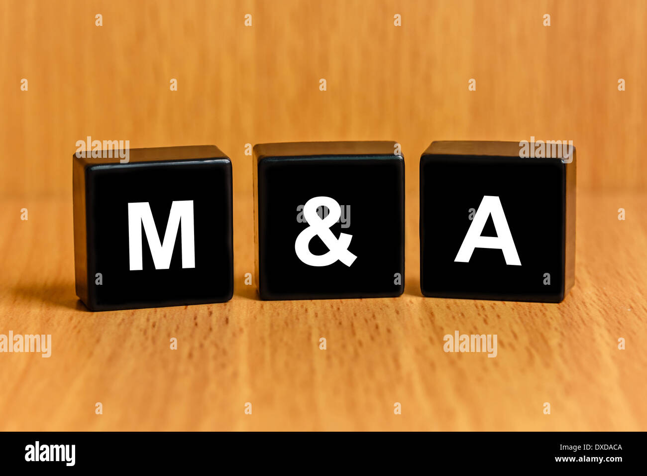 M&A or Merger and Acquisition text on black block - Stock Image