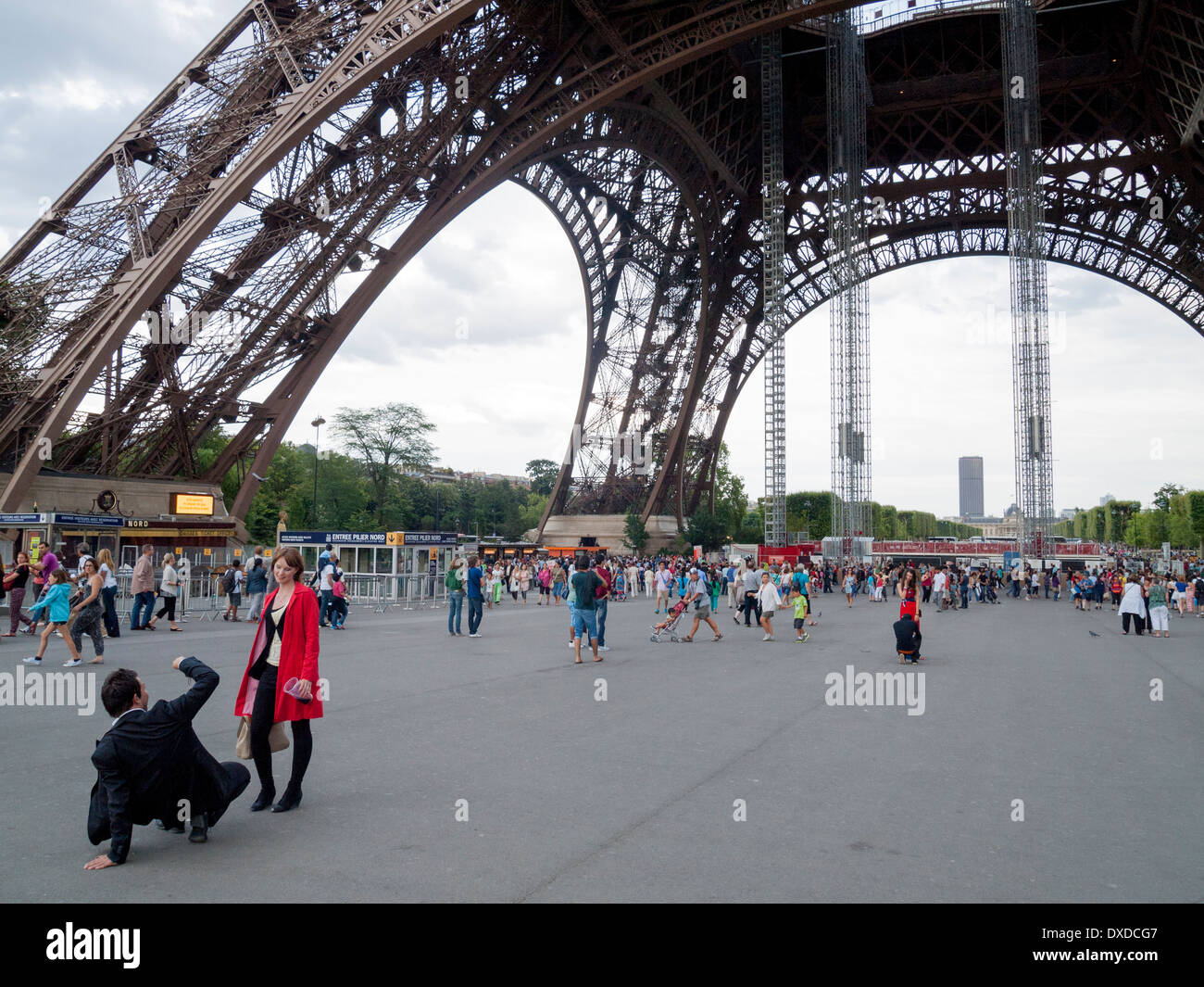 Eiffel Tower in Paris France. Man taking photograph of girlfriend. - Stock Image