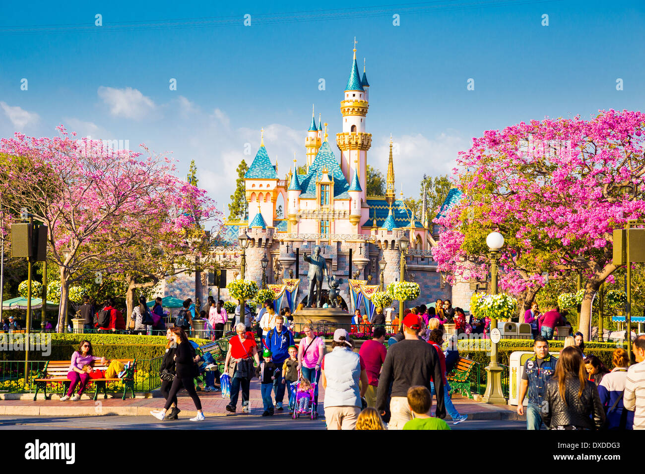 Disneyland Main Street crowded with guests and a tram car in the road leading towards the iconic pink castle. Stock Photo