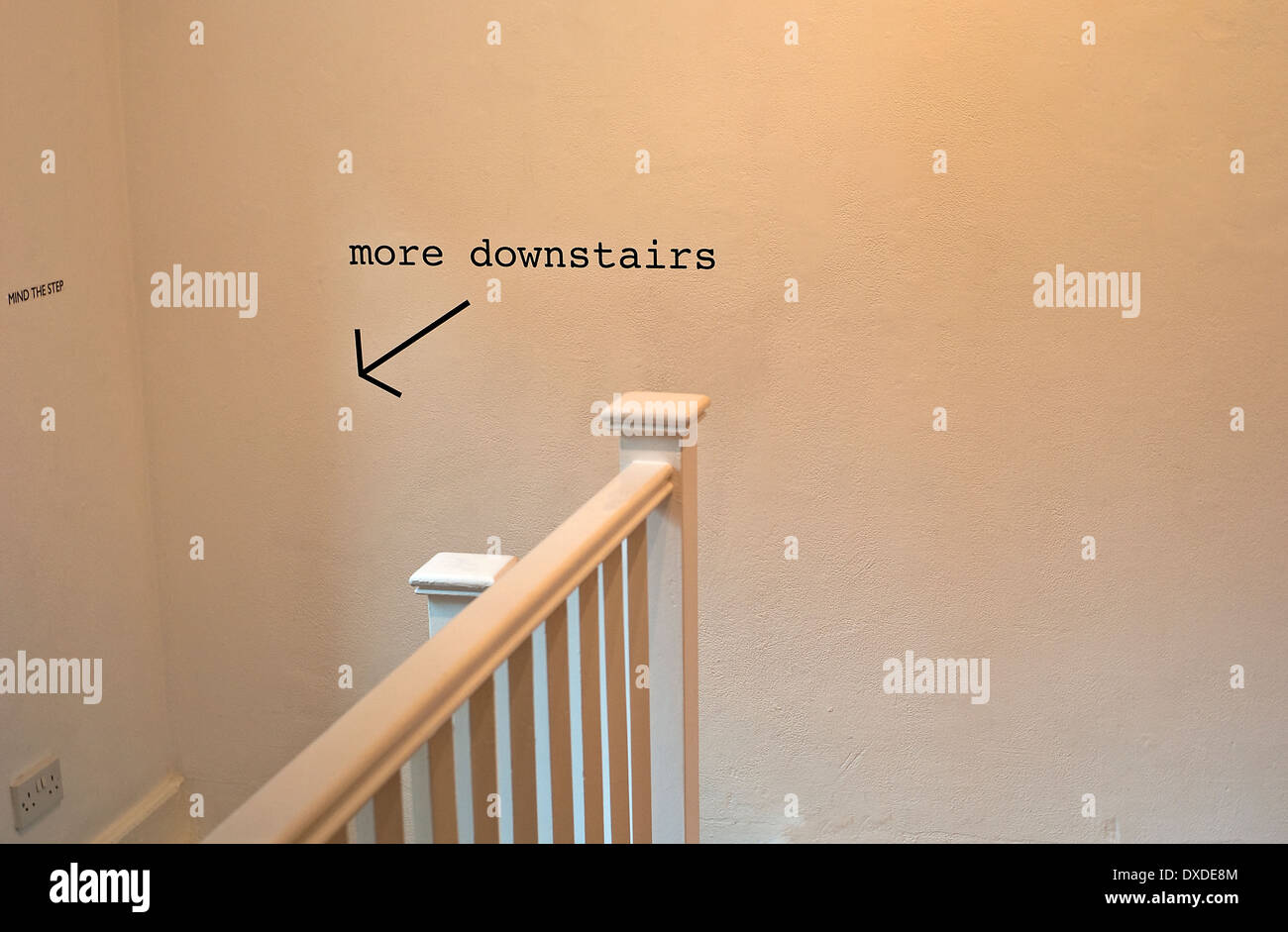 More downstairs sign with arrow - Stock Image