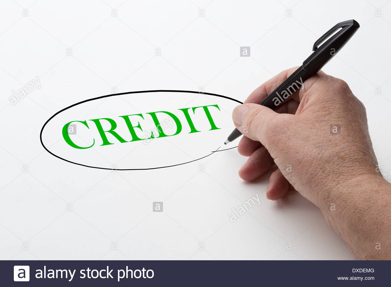 Man hand holding a black pen and encircling the word credit. - Stock Image