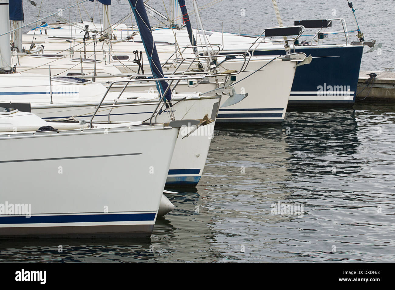Used sail boats or yachts in a row for sale in a marina which buys and sells sailing equipment. - Stock Image