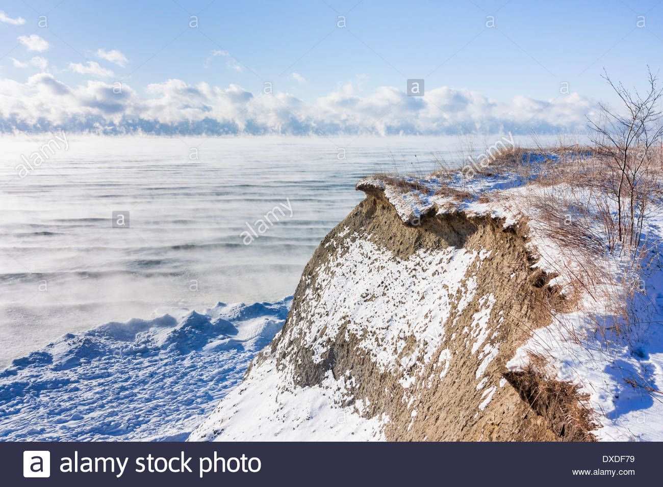 Sea smoke condenses over open Lake Ontario on a windy cold -20C winter day at the Scarborough Bluffs in Toronto Ontario Canada - Stock Image