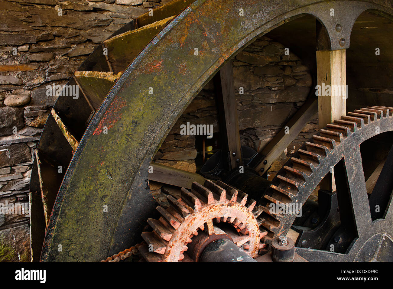 Enclosed water mill wheel workings with ancient metal and wooden cog system part of industrial heritage. - Stock Image
