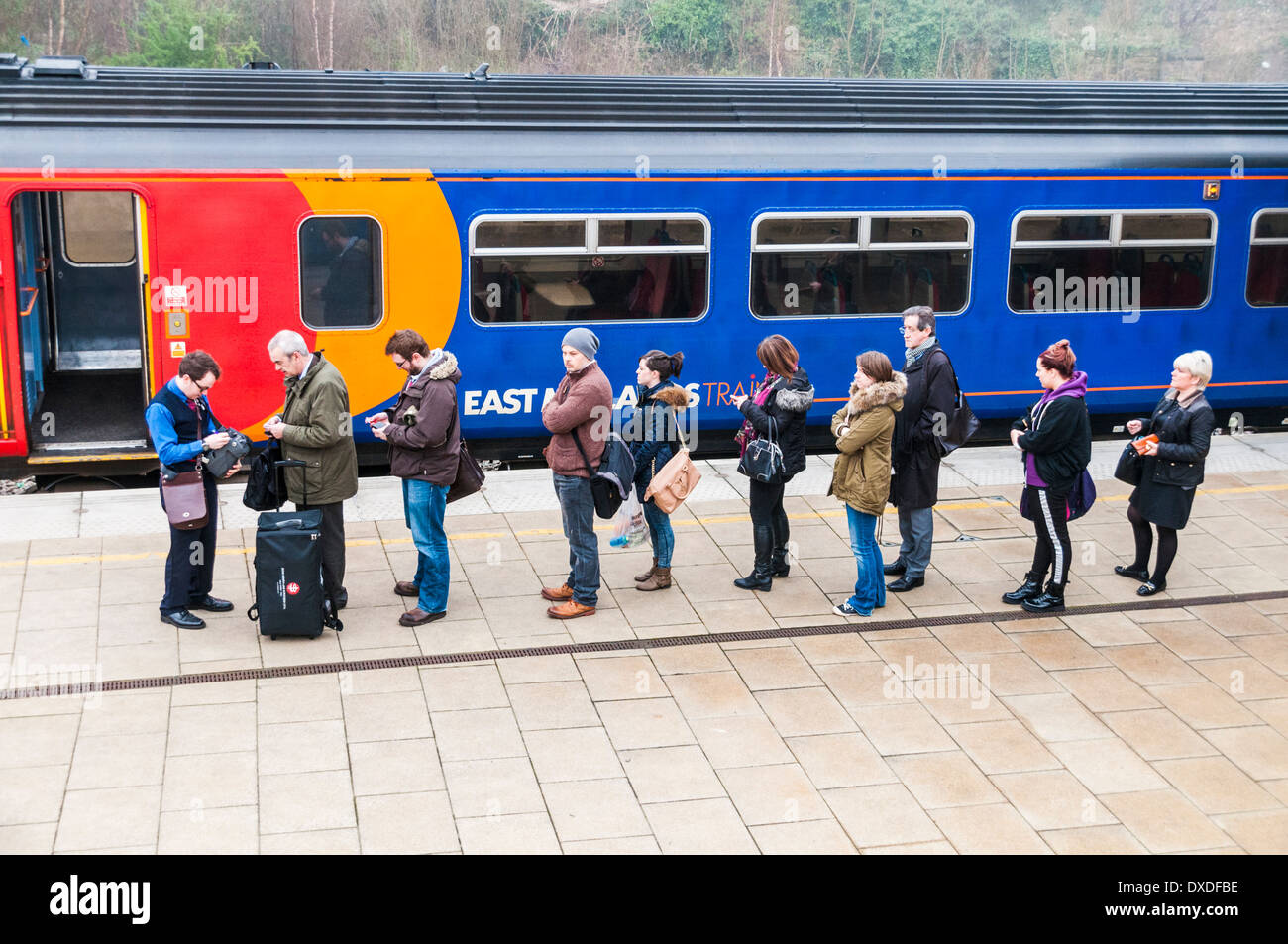 A queue of people getting tickets from a train guard on the platform at Leicester station before boarding an East Midlands Train - Stock Image