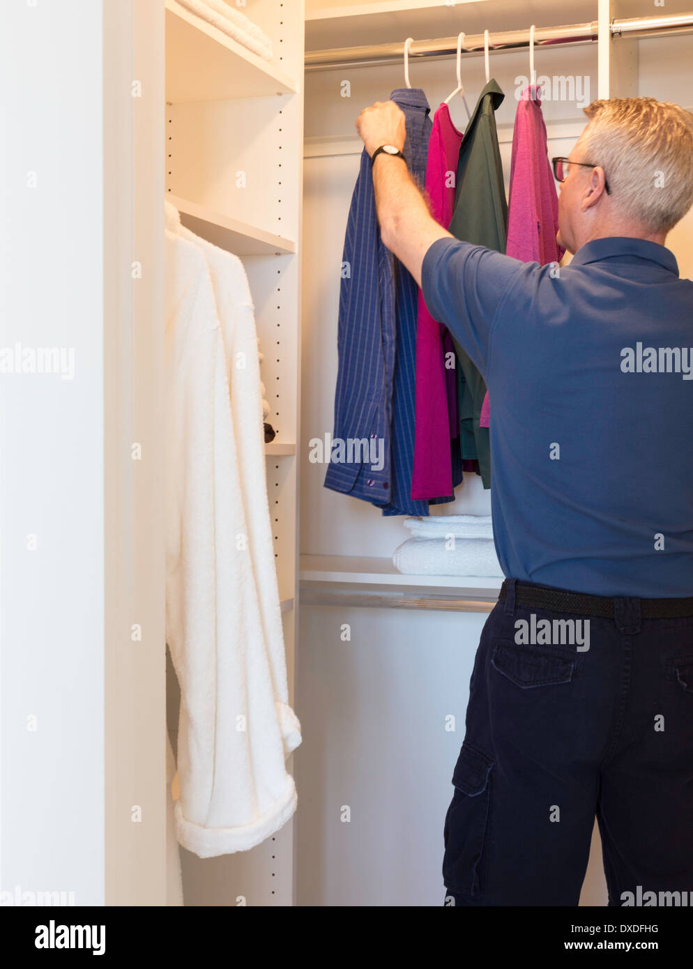 Beau Mature Man Reaching For Hanging Clothes In Walk In Closet, USA   Stock Image