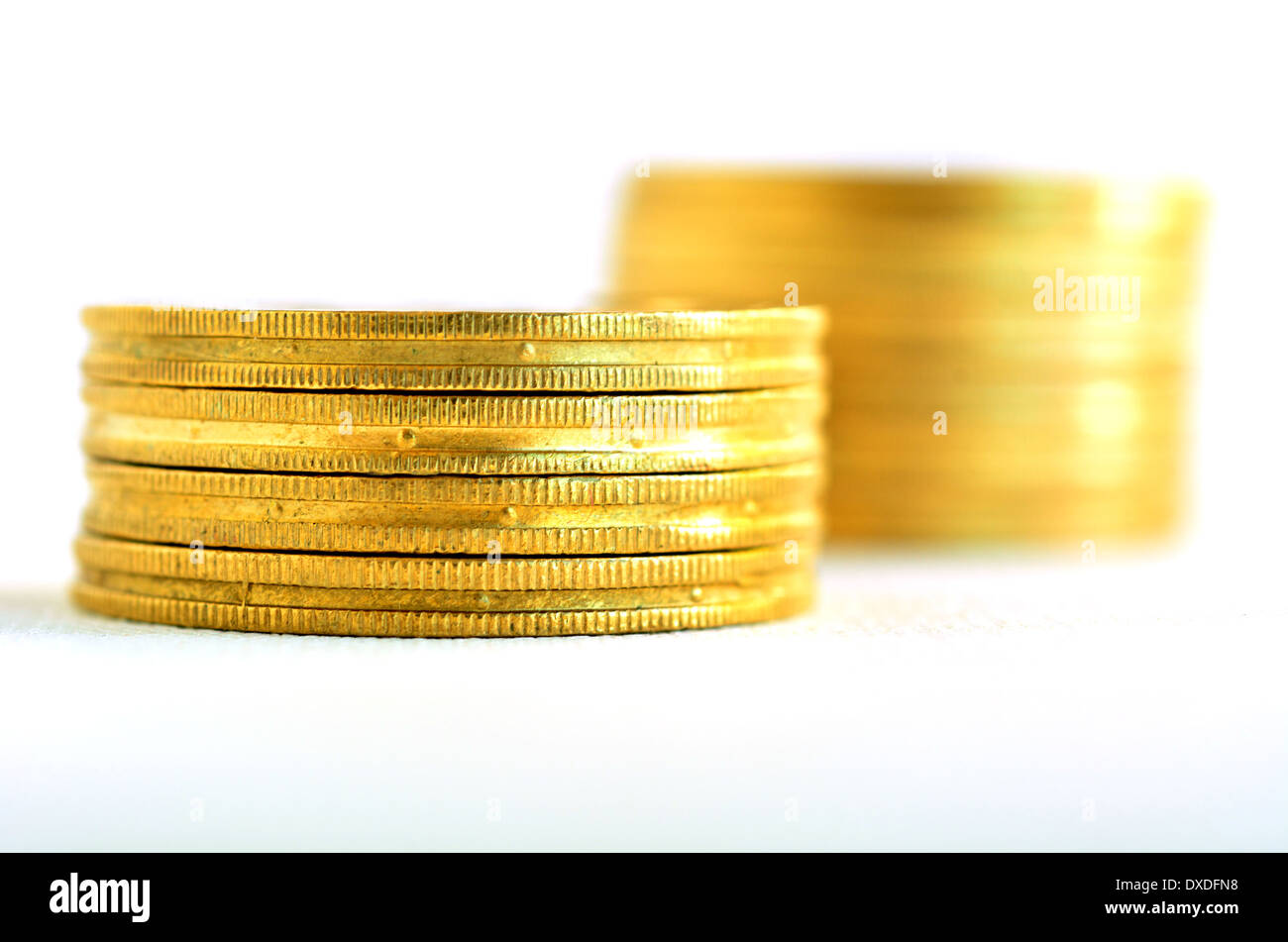 Two small Golden gold coins stacks isolated on white background. Concept photo - Stock Image