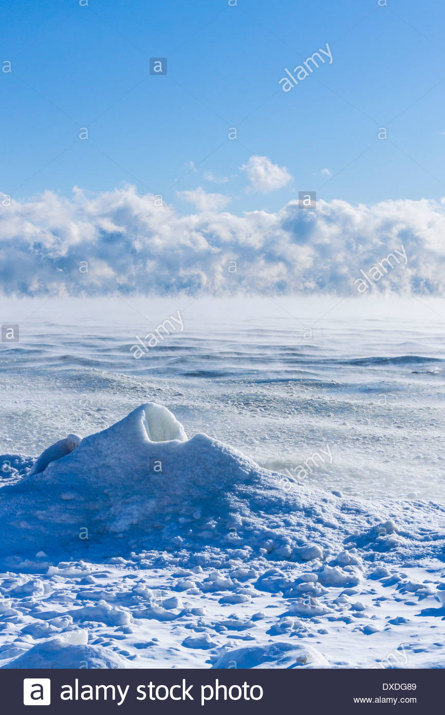 Sea smoke condenses over waters of open Lake Ontario on a cold windy -20C day at Eastpoint Park in Toronto Ontario Canada - Stock Image