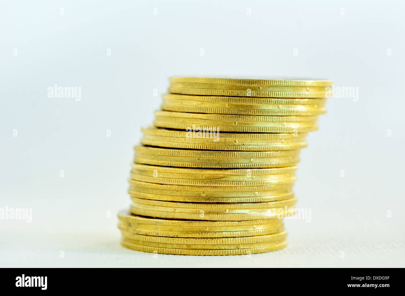 One Golden gold coins stack on a lean, isolated on white background. Concept photo of bank, money, banking, finance, economy. - Stock Image