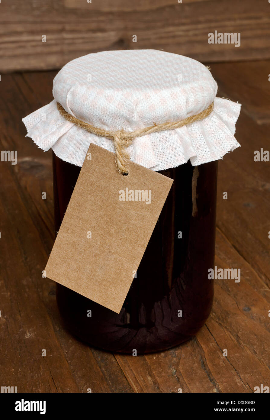 Mixed fruit jam in a glass jar with traditional cloth lid and blank label for insertion of your message or company branding. - Stock Image