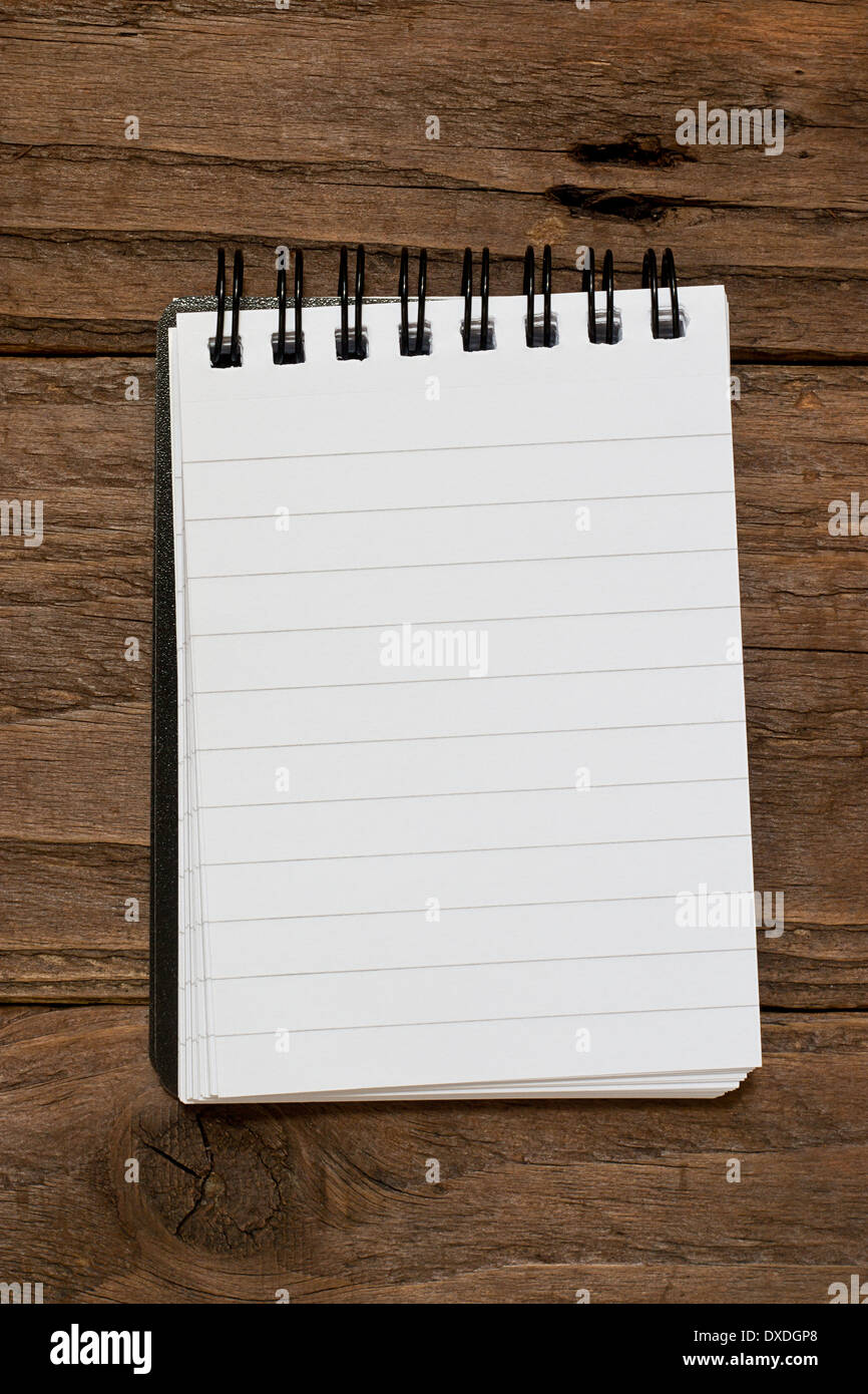Small pocket sized notepad on a rustic wooden background with blank space for inserting your own message or note. - Stock Image