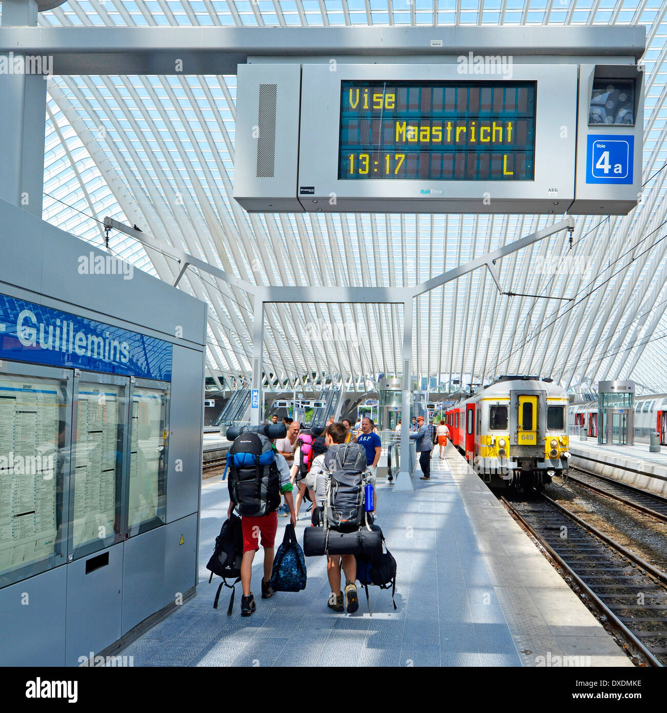 Backpackers group train station platform loaded with backpack kit in modern public transport glass roof building departures board Belgium Liege - Stock Image