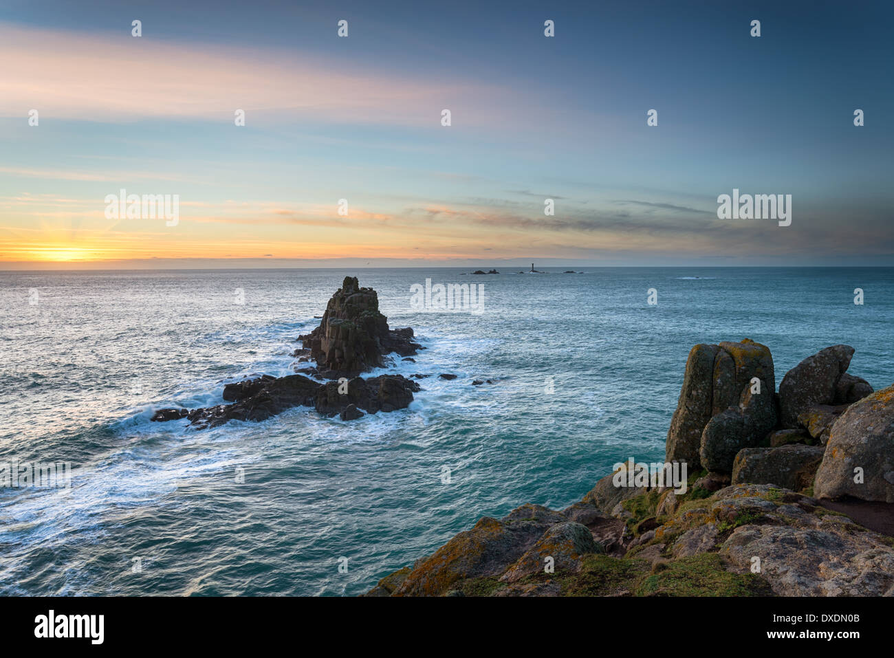 Rocky cliffs and sea stacks at Lands End in Cornwall with the Longships lighthouse in the distance - Stock Image