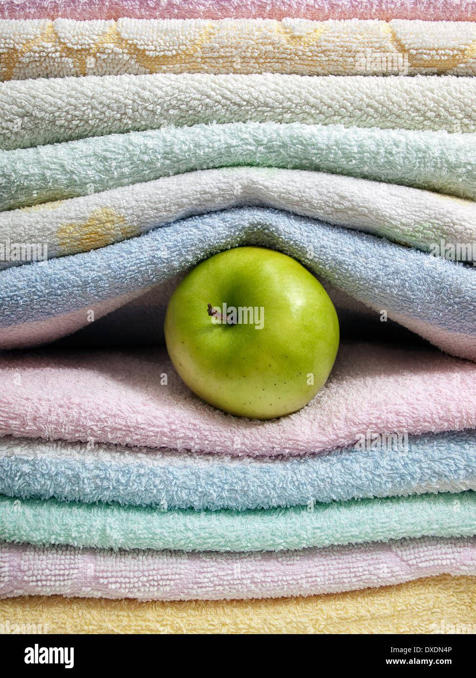 Apple between sorted towels as a concept of cleanliness and hygiene. - Stock Image