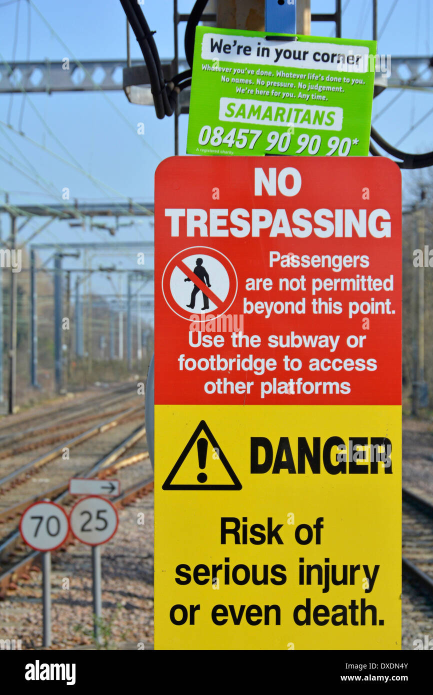 Samaritans contact notice wedged into the top of warning signs on station platform beside railway tracks - Stock Image