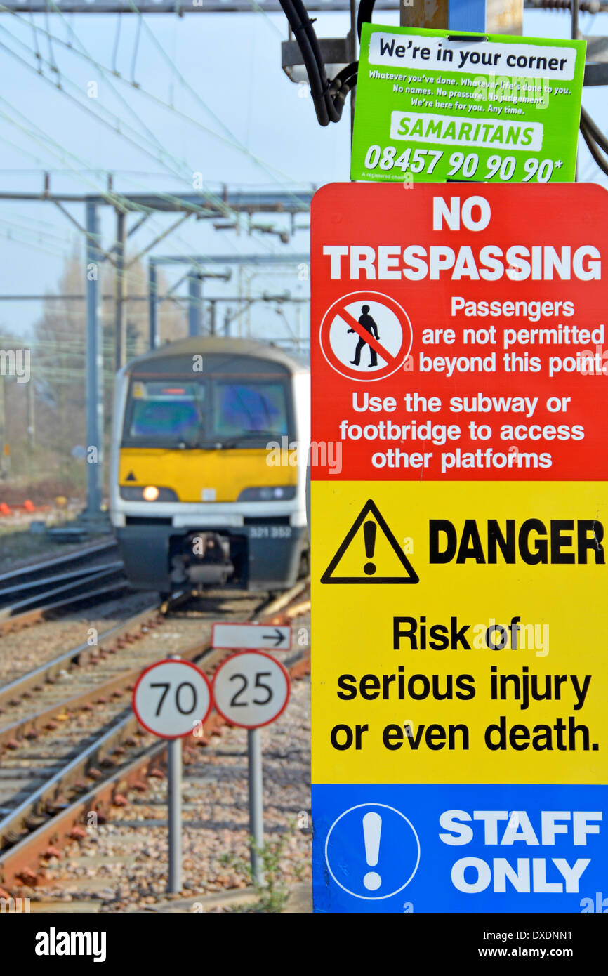 Samaritans contact notice wedged into the top of warning signs on station platform with train approaching - Stock Image