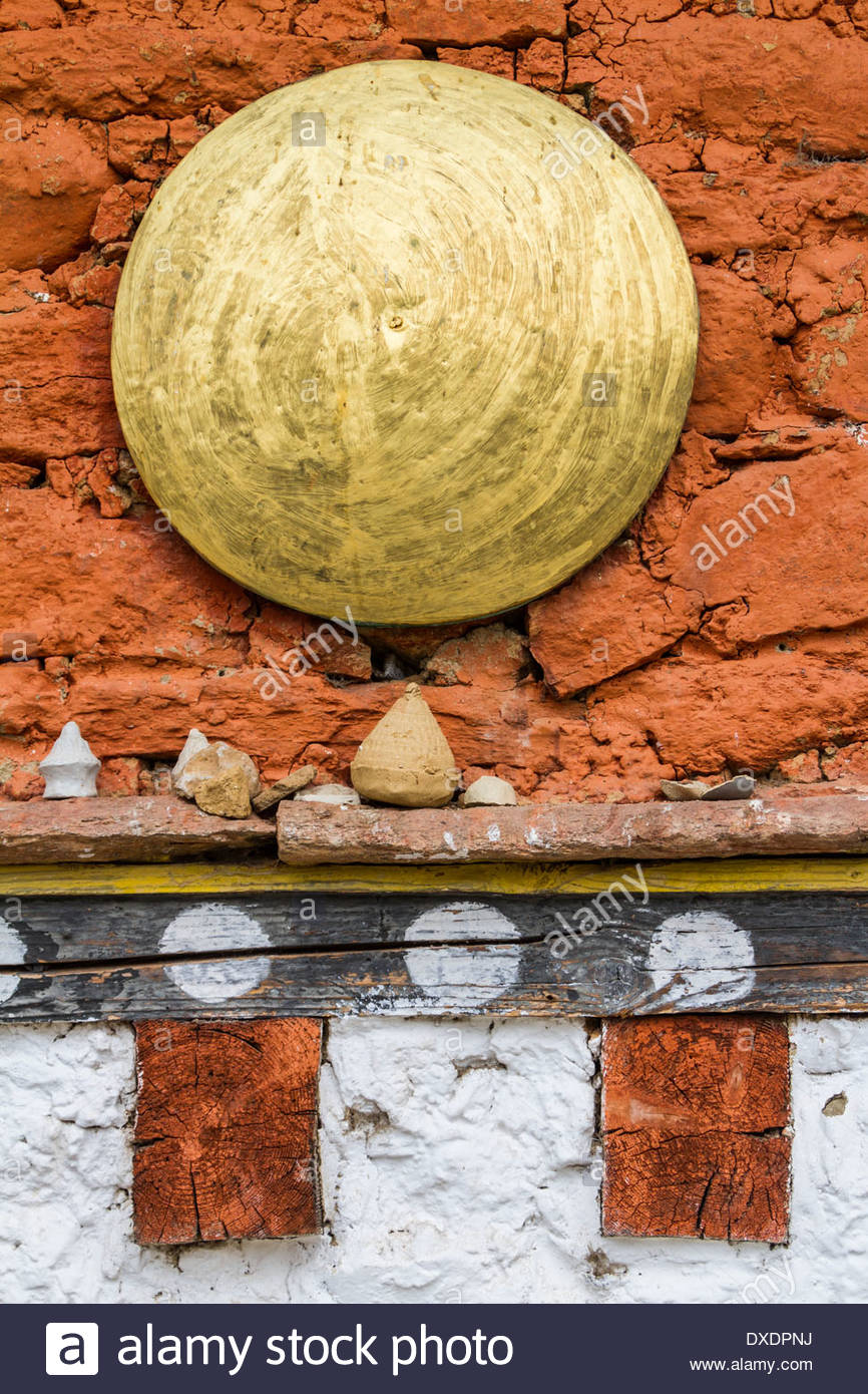 A gold disc sits above some tsa tsas at a temple in Bhutan - Stock Image