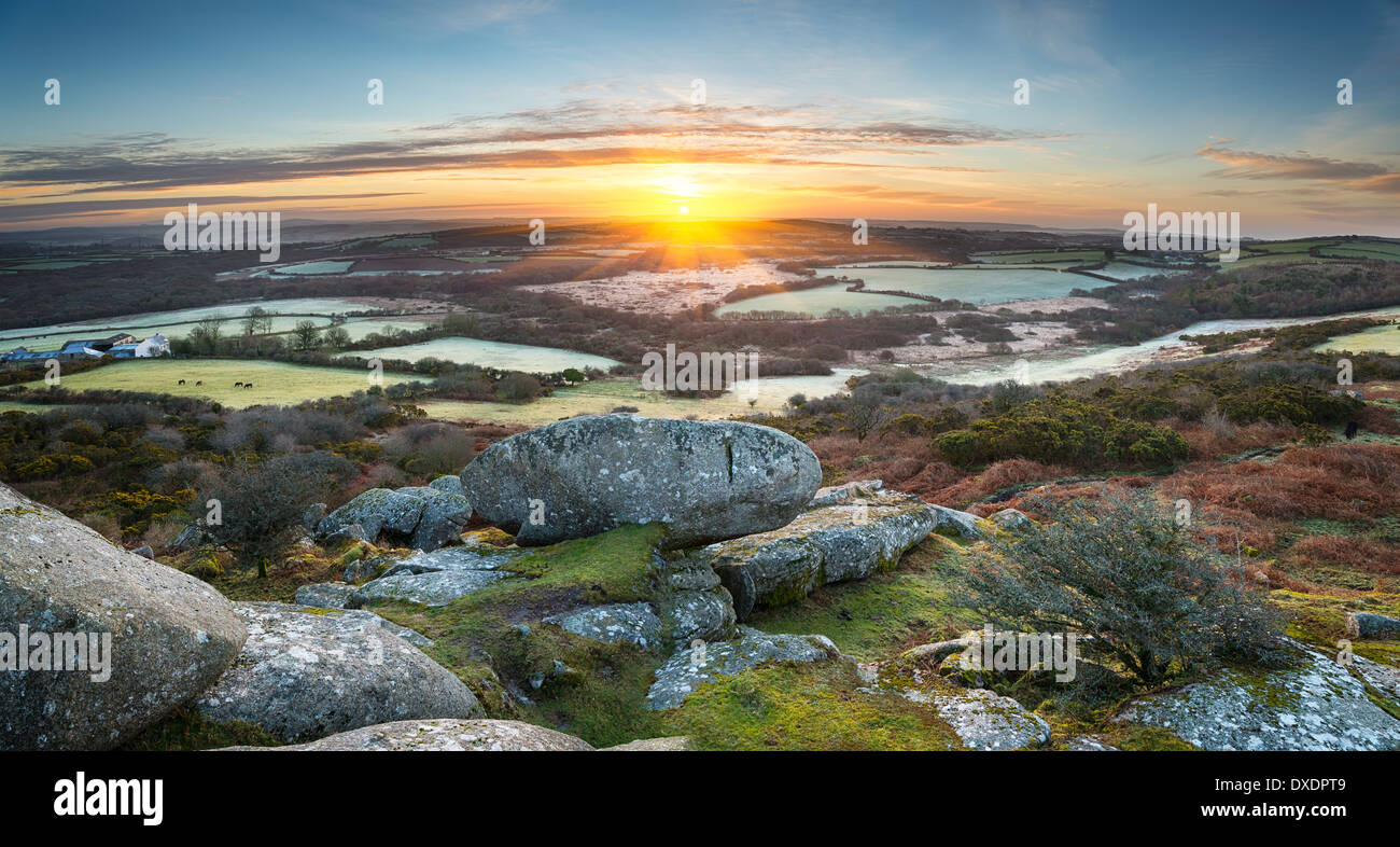 A frosty early spring sunrise looking out over a patchwork of fields and rolling hills at Helman Tor a rocky outcrop of rugged m - Stock Image