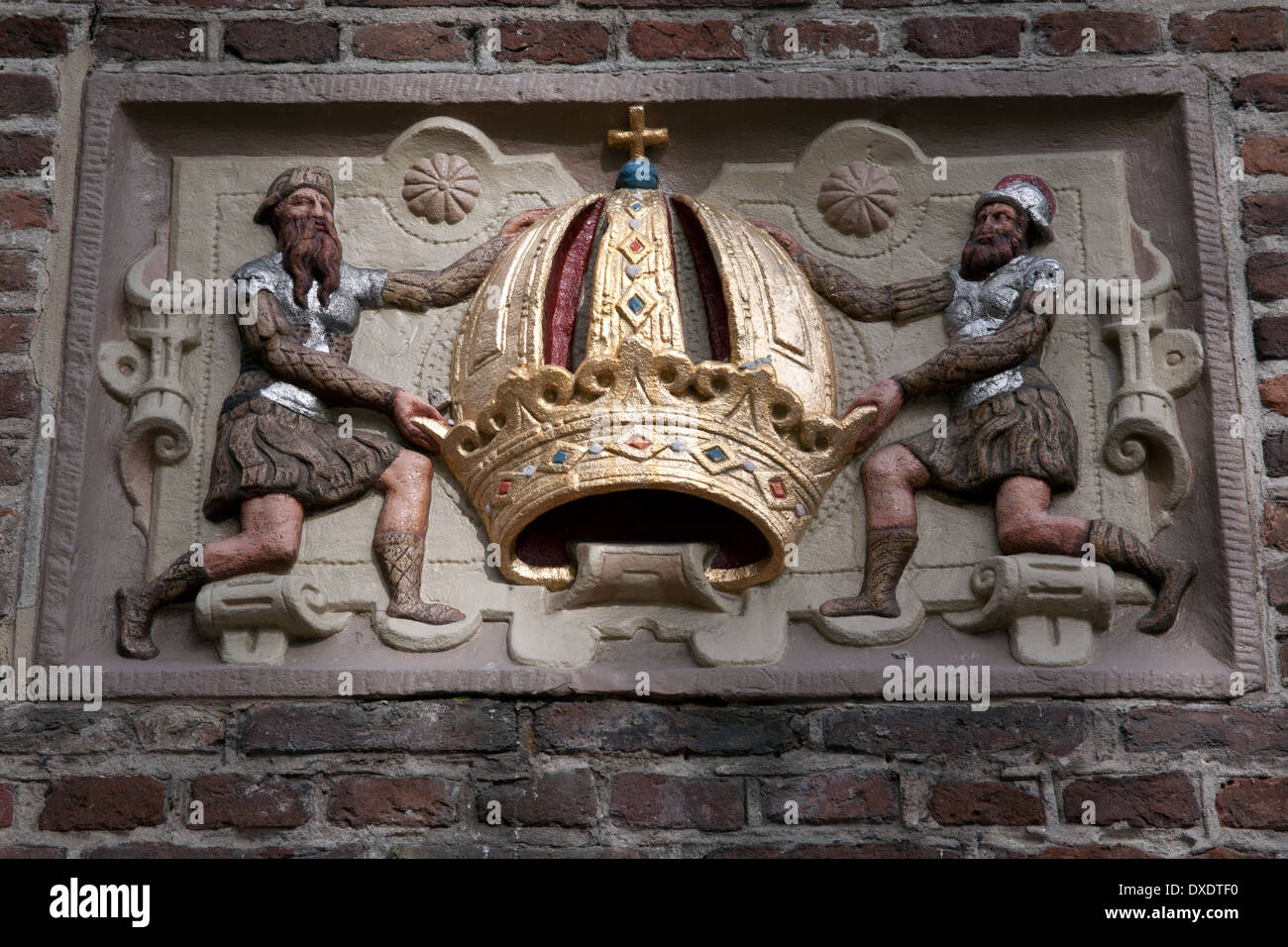 Soldiers holding a crown, a wall tile or gevelsteen in Amsterdam the Netherlands - Stock Image