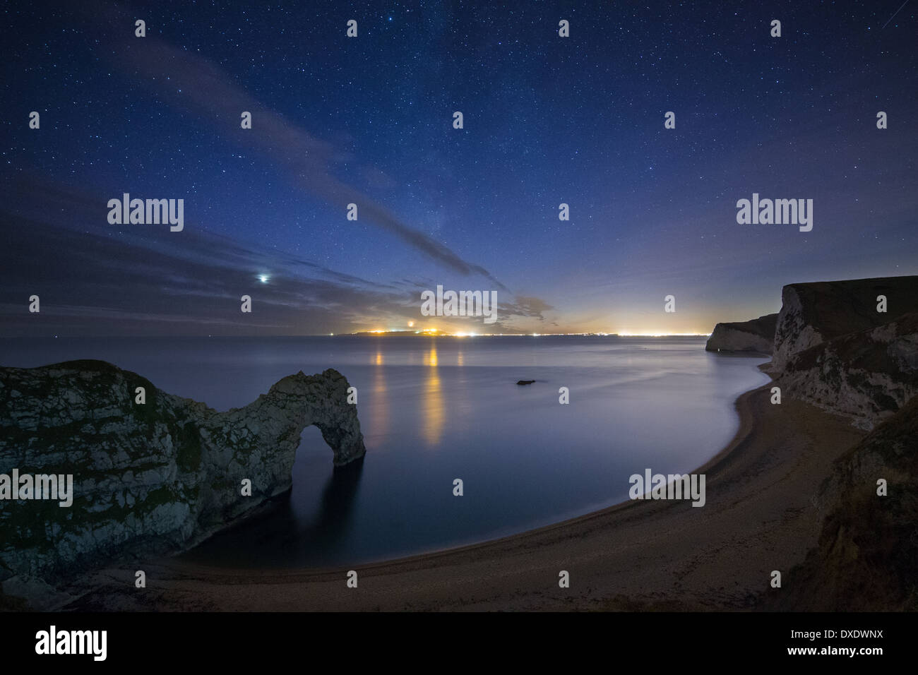 the stars and Milky Way over Durdle Door and the Jurassic Coast, with the lights of Weymouth & Portland beyond, Dorset, England - Stock Image