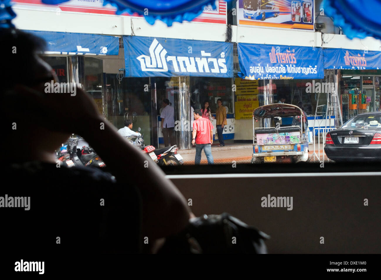 A view fom a songthaew includes people leading their daily lives on a city street in Khorat, (Nakon Ratchasima) Thailand. - Stock Image
