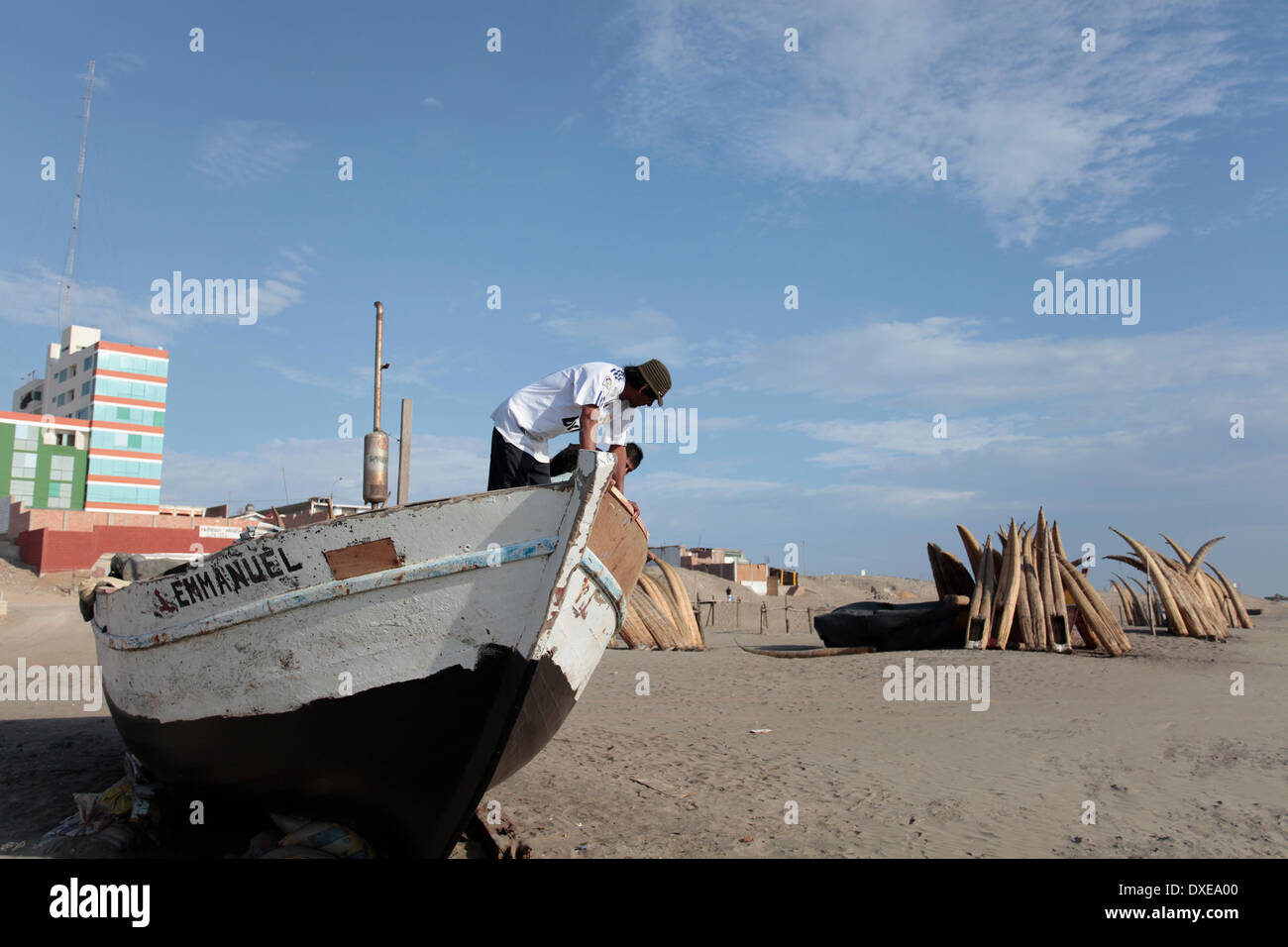PIMENTEL, PERU- MARCH 22: Several men are repairing a small fishing boat on the beach of Pimentel, some 800 km to the N of Lima, in Pimentel, Peru, Saturday, March 22, 2014. Photo by Elkin Cabarcas - Stock Image