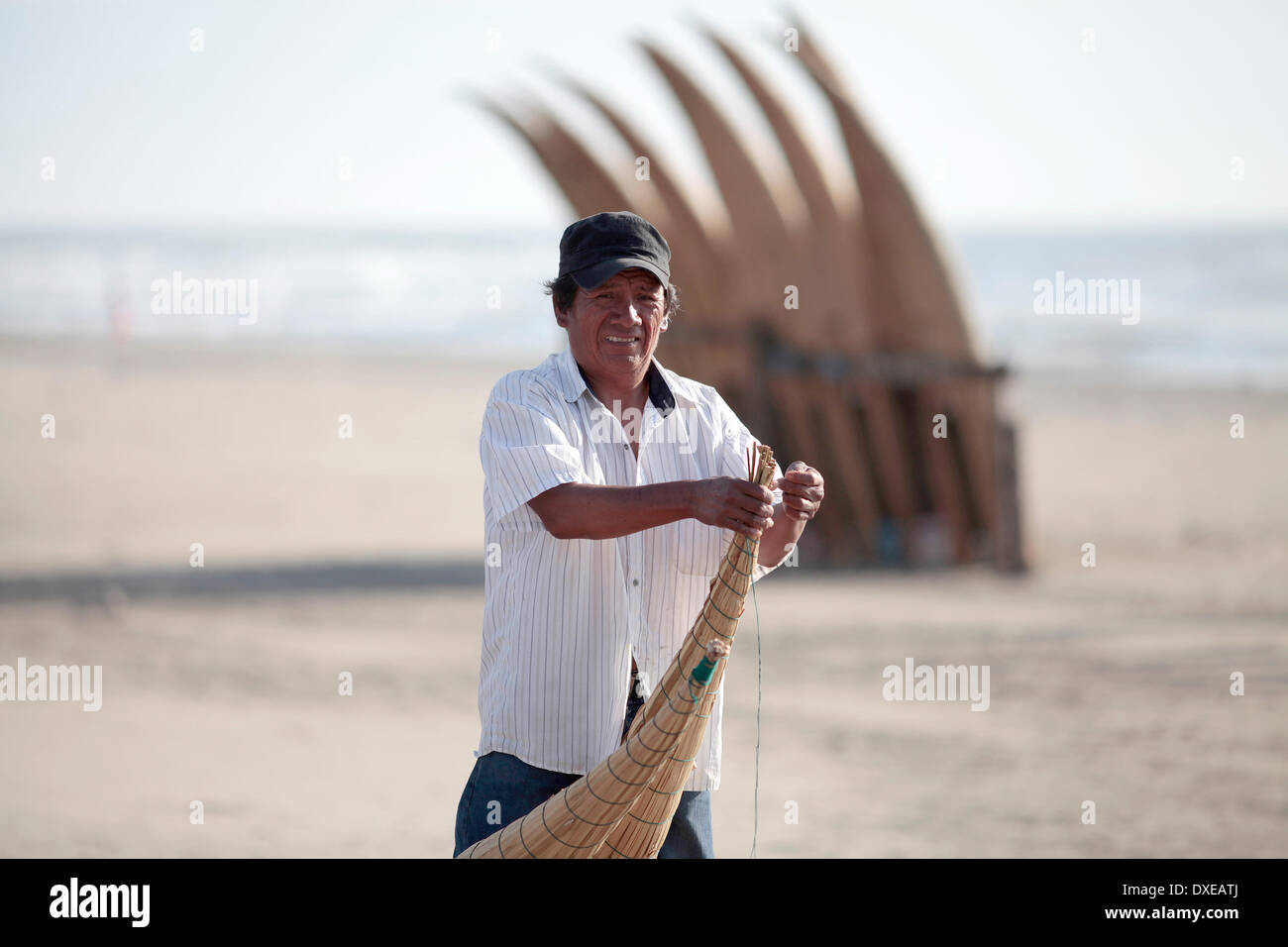 PIMENTEL, PERU - MARCH 22: Jorge a fisherman in 'Totora Horses' is seen on the beach of Pimentel repair damage suffered in 'Totora Horses' after a day of fishing in Pacific Ocean, about 800 kilometers north of Lima in Pimentel, Peru, Saturday, March 22, 2014. The 'Totora Horses' are Built with cattail rushes like the ethnic group of the Inca empire Mochica already made five centuries ago. The canoes are used daily to go deep into the ocean, to return after working for Between 8 and 12 hours with 50 kg of fish trapped with nets. Today fishing tends to decrease and thus the income of fisherfolk. - Stock Image